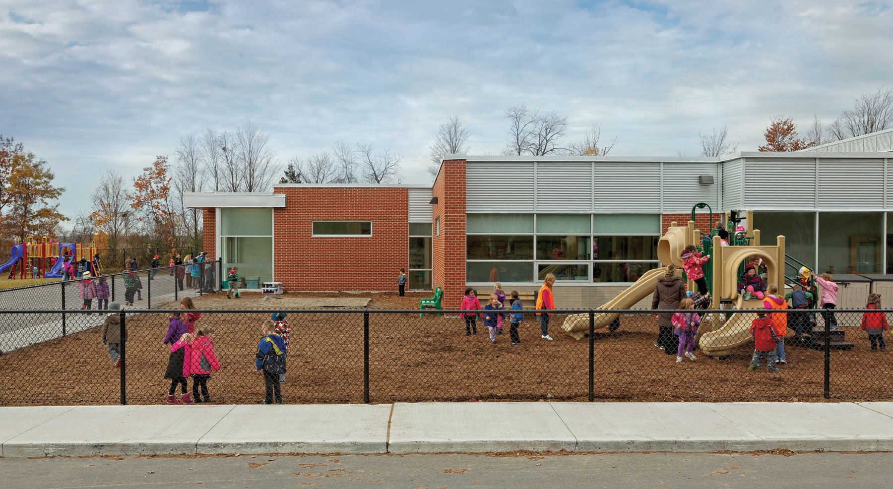 Students playing on playground at recess with elevation of school in background