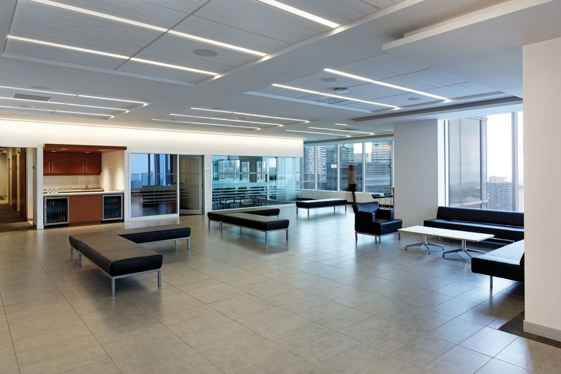 Student lounge area with soft bench seating, kitchenette, glazed meeting room and perimeter windows with views of lake and city from 30th floor