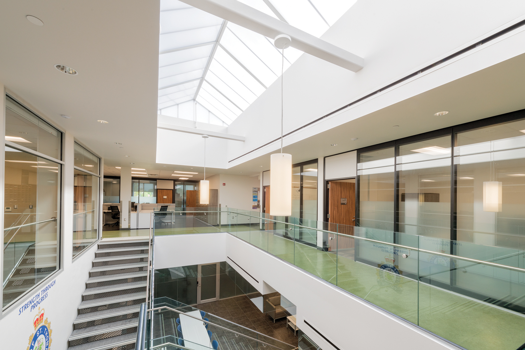 Open staircase leading to second storey perimeter corridor with glazed meeting rooms and large skylight
