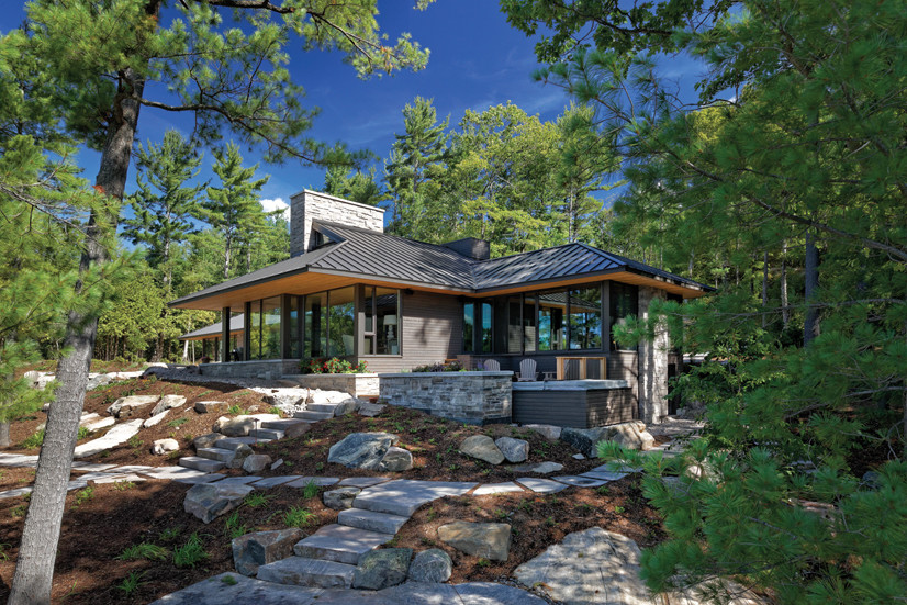 Cottage nestled in trees surrounded by rock landscaping on a sunny day