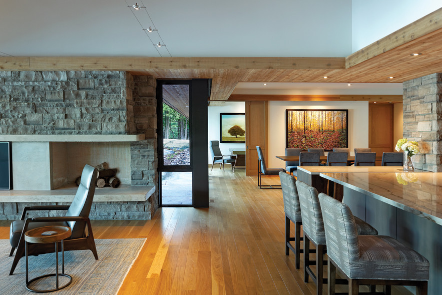Open concept living room with stone fireplace, kitchen and dining area