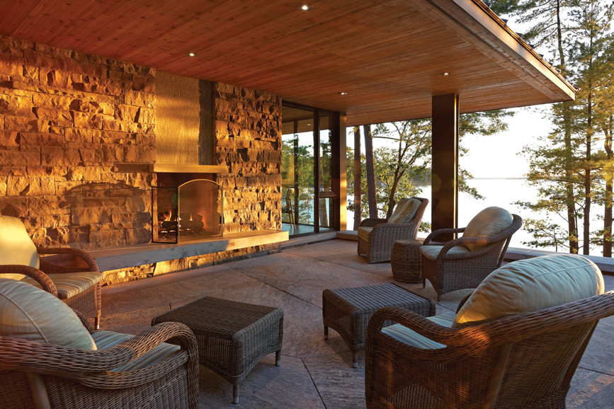 Covered porch with wicker seating and stone wall fireplace feature and views of lake and trees at sunset