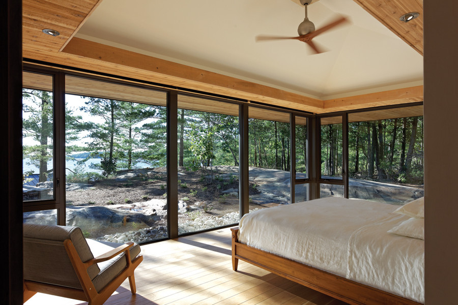 Bedroom with glazed walls looking out to rock landscaping, trees and lake beyond