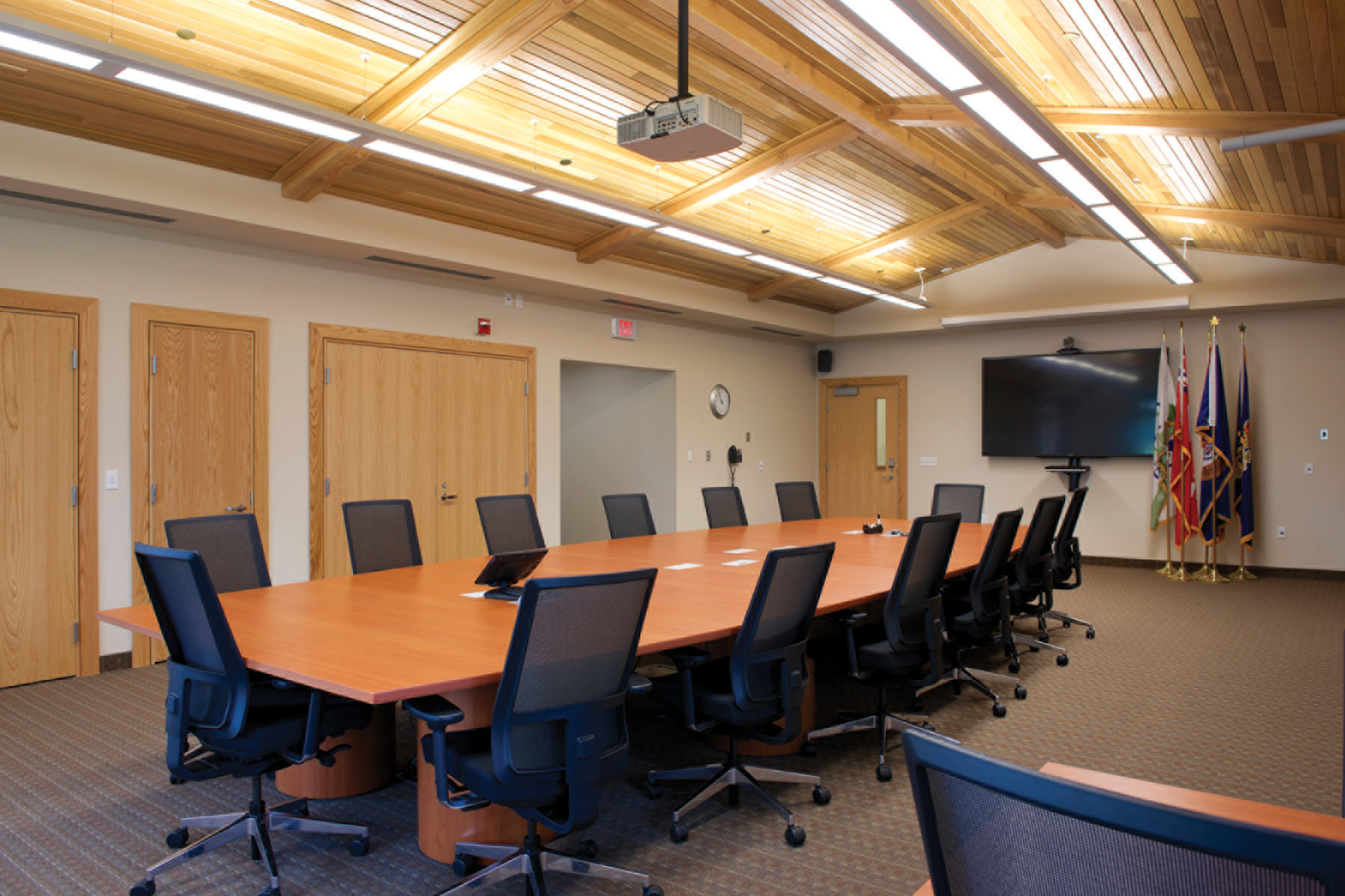 Board room with black mesh back chairs, slanted wood panel ceiling, hanging projector, TV and flag poles