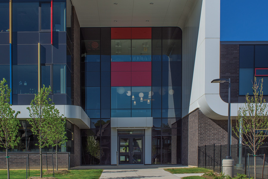 Triple height front entrance with red, yellow and blue glazing and white framing