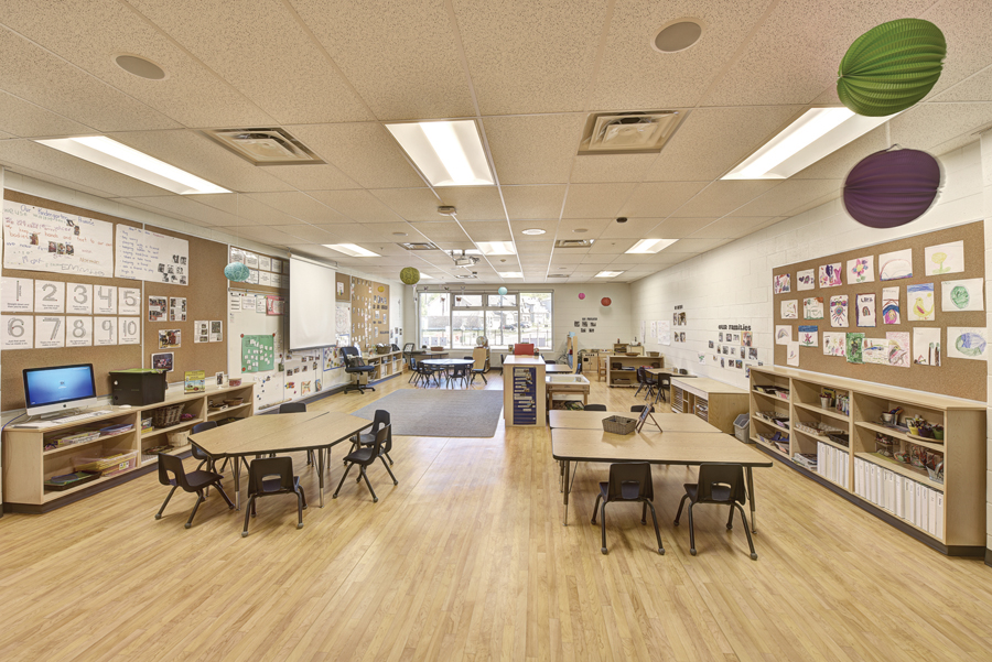 Kindergarten classroom with group seating, computer work station, play area and green and purple hanging paper lanterns