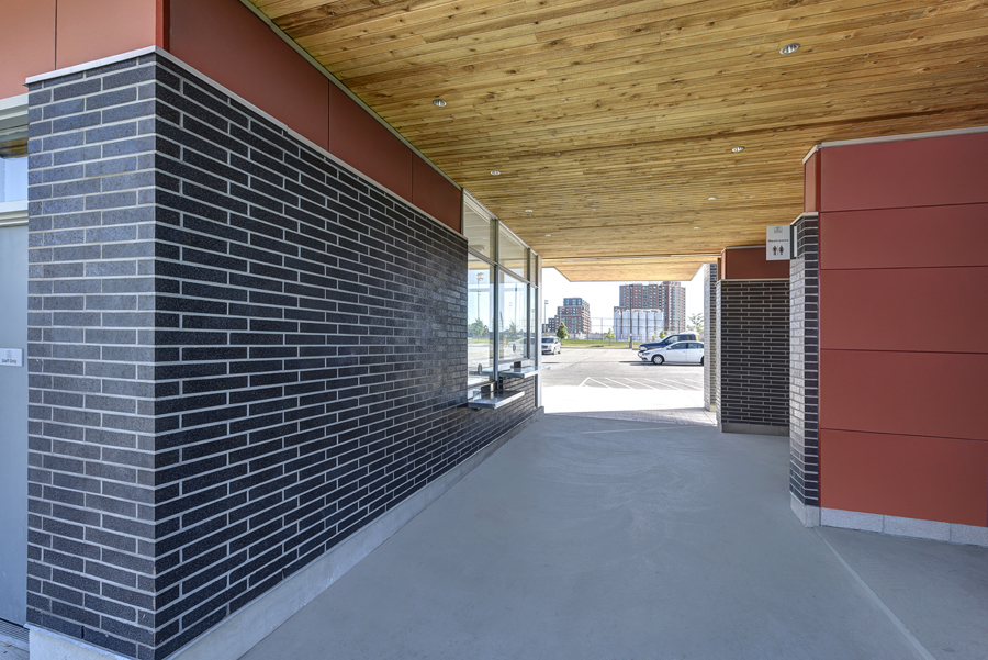 Gateway entrance with ticket booth and grey brick and wood cantilevered ceiling