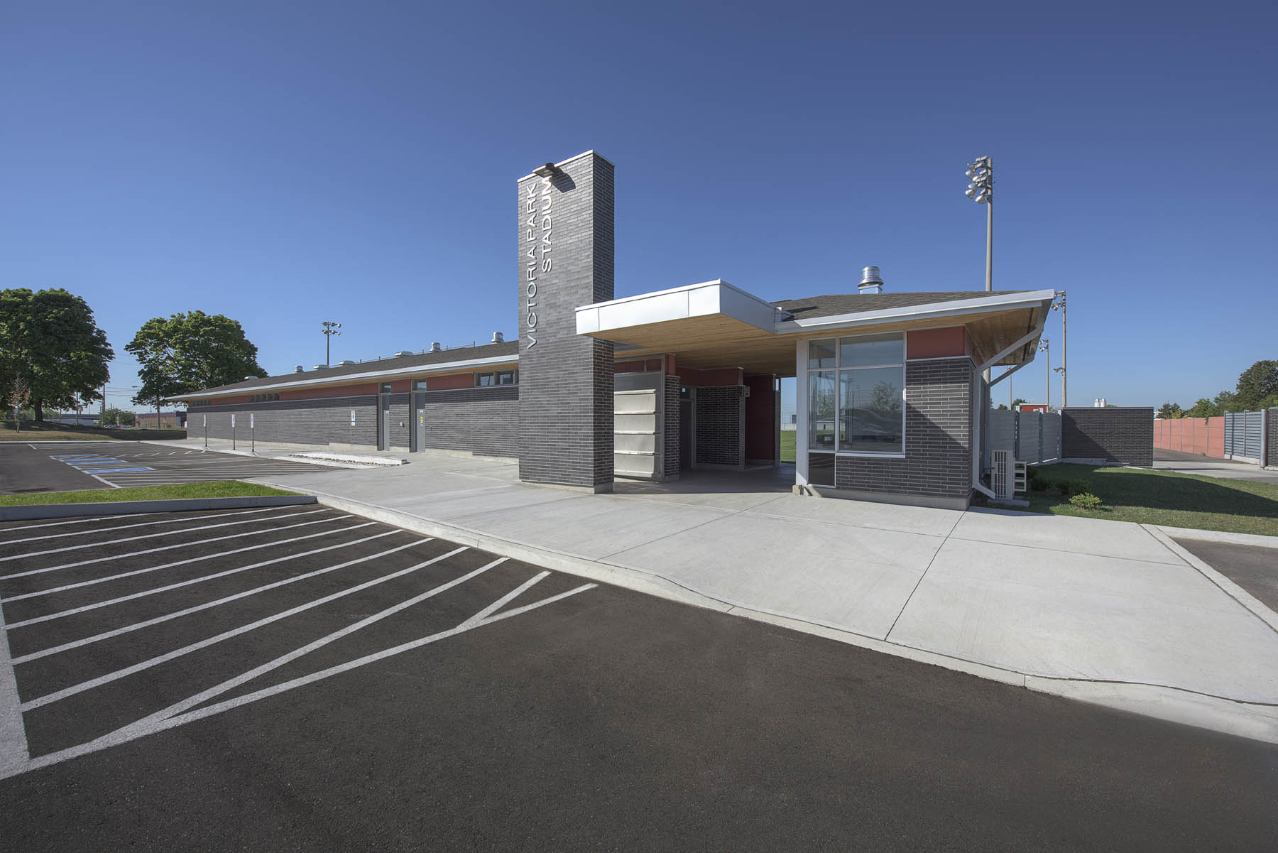 View of fieldhouse from parking lot with cantilevered gateway entrance with tall grey brick column with signage