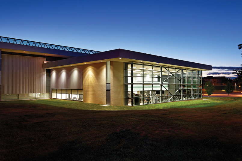 View of glazed front façade showing illuminated double height fitness area from grassy lawn at dawn