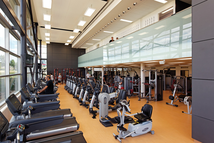 Glazed double height fitness area with treadmills and exercise bikes and second storey corridor with glass guard rail