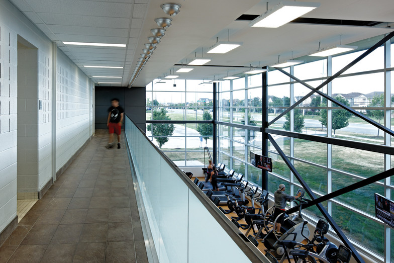 View of glazed double height fitness area from second storey corridor with glass guard rail