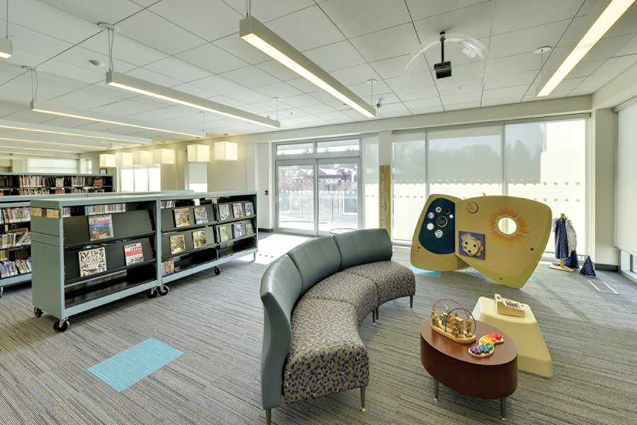Kids lounge space with play structure, blue chairs, bookshelves and windows in background