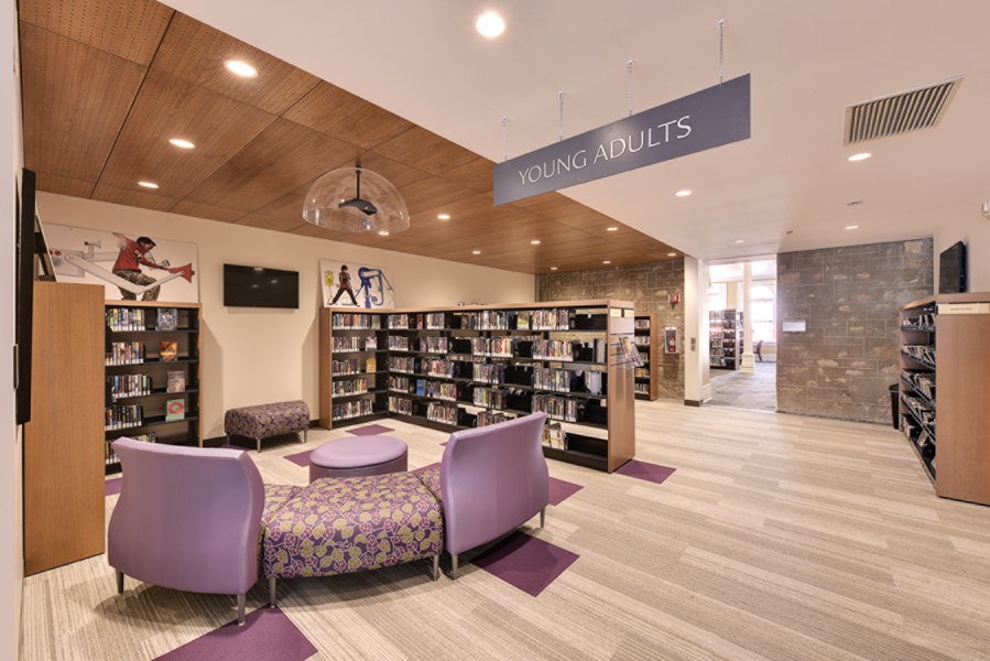 Young Adults reading lounge area with purple chairs, wood ceiling feature and bookshelves