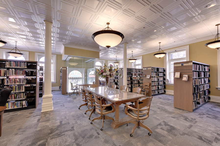 Communal wood table and chairs with white pendant lights, white pillars and bookshelves with arched entrance and windows in background