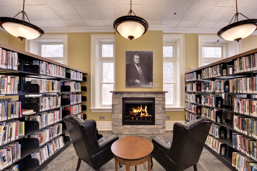 Lounge space with large leather chairs, fireplace, white pendant lighting, bookshelves and large vertical rectangular windows