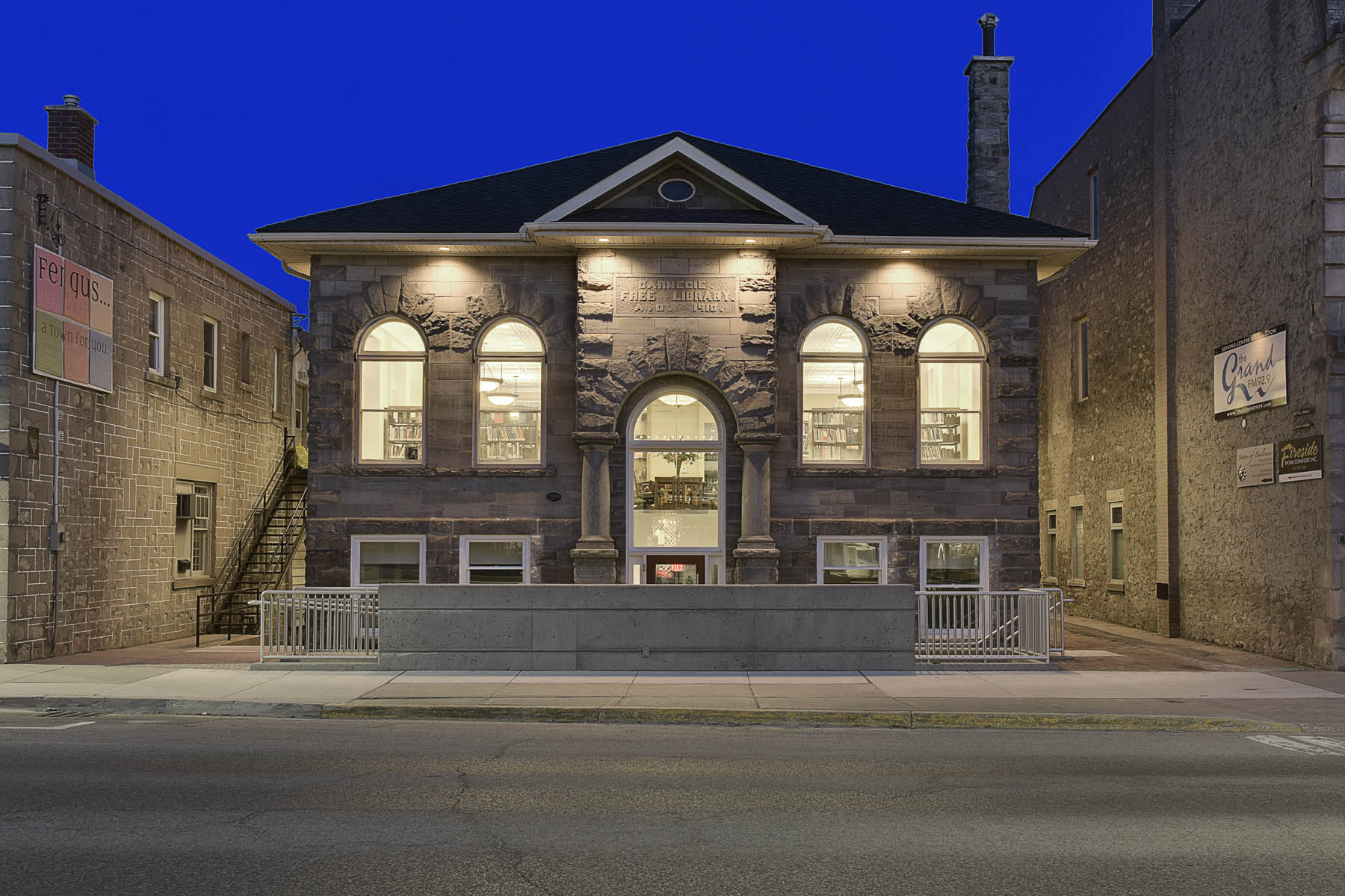 View of illuminated stone front façade from across the street at dusk featuring archway entrance and windows