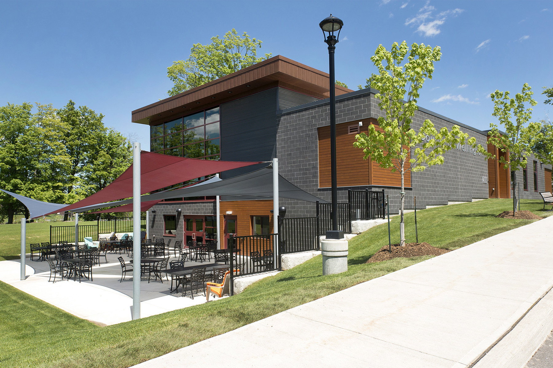 View of double height glazed addition from sidewalk with canopy covered patio seating