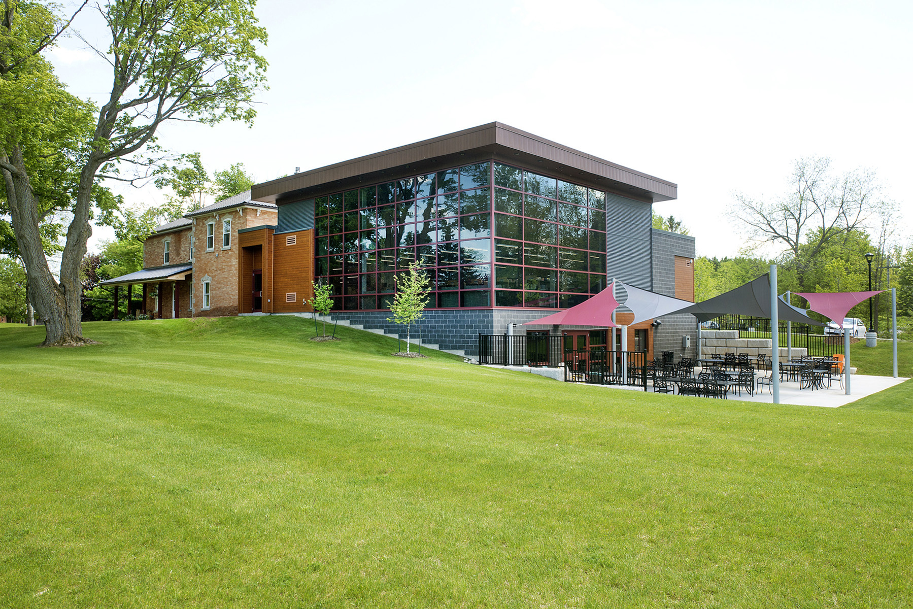 View of double height glazed addition from green lawn with canopy covered patio seating