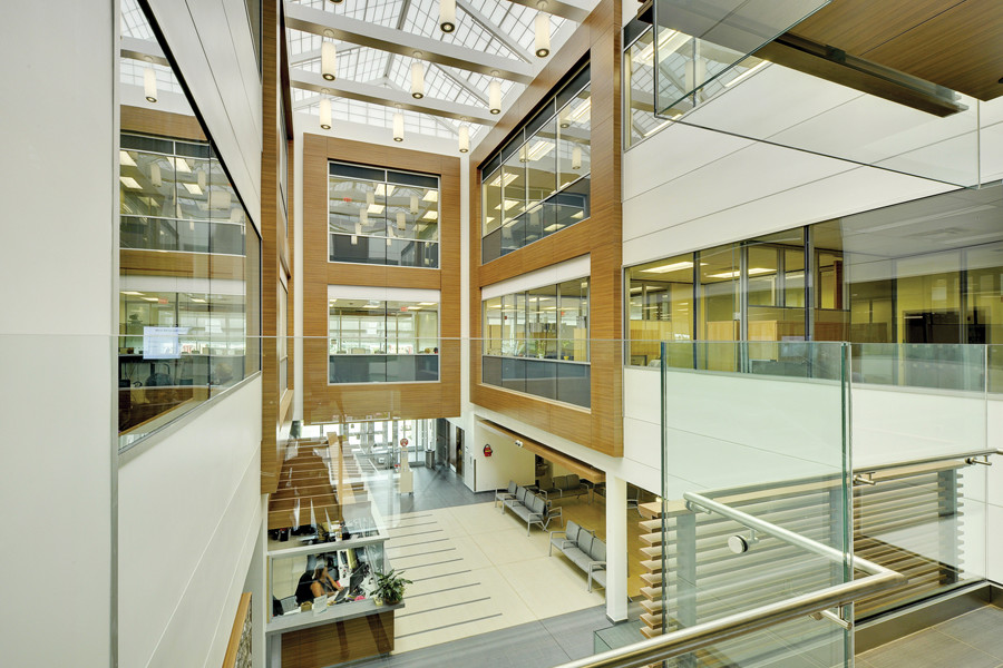 Triple height atrium space with skylight, white pendant lights and glazed corridors