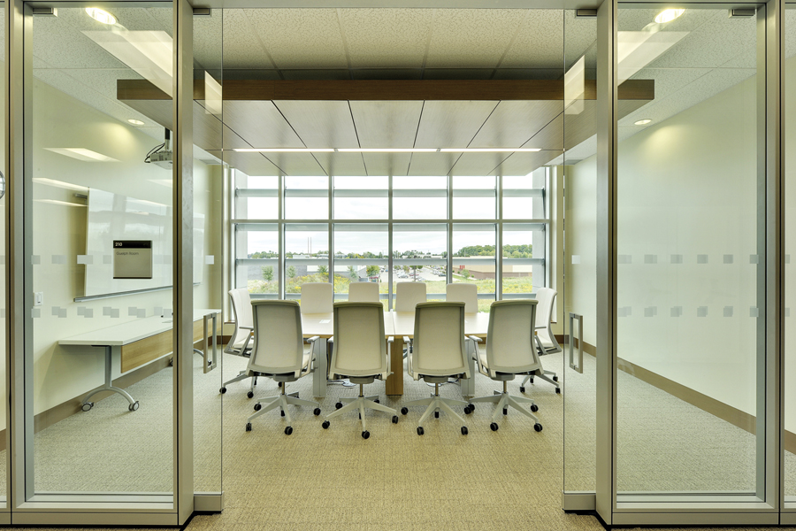 Glazed white meeting room with sliding glass doors, white mesh back chairs, white board, and wooden ceiling feature