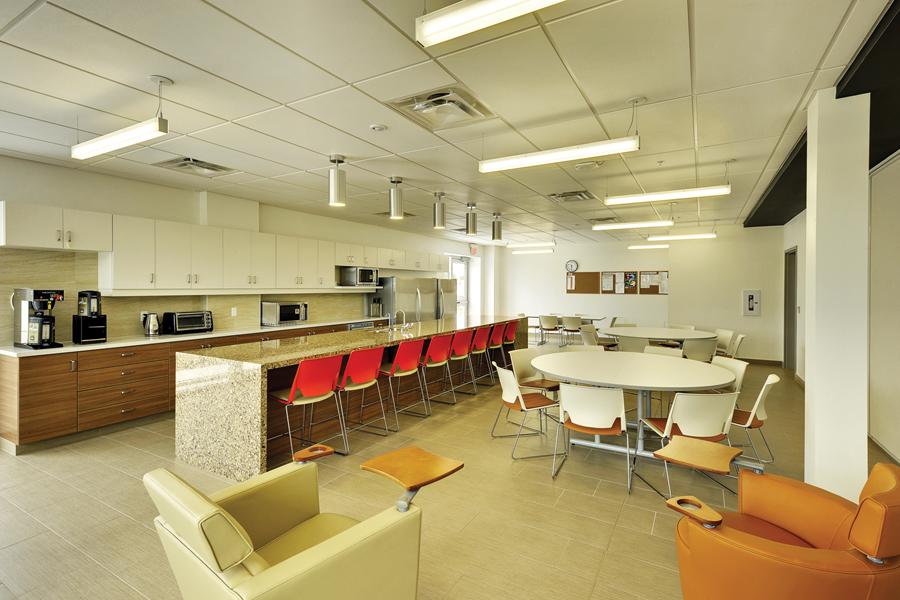 Staff lounge area with kitchenette, island with red high back stools, white circular tables and cream and tan leather lounge chairs