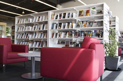 Reading area with red lounge chairs and white bookshelves in background with sun casting shadows on the floor