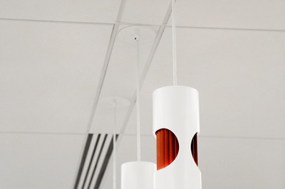 Detail shot of three white cylindrical pendant light fixtures with red detail