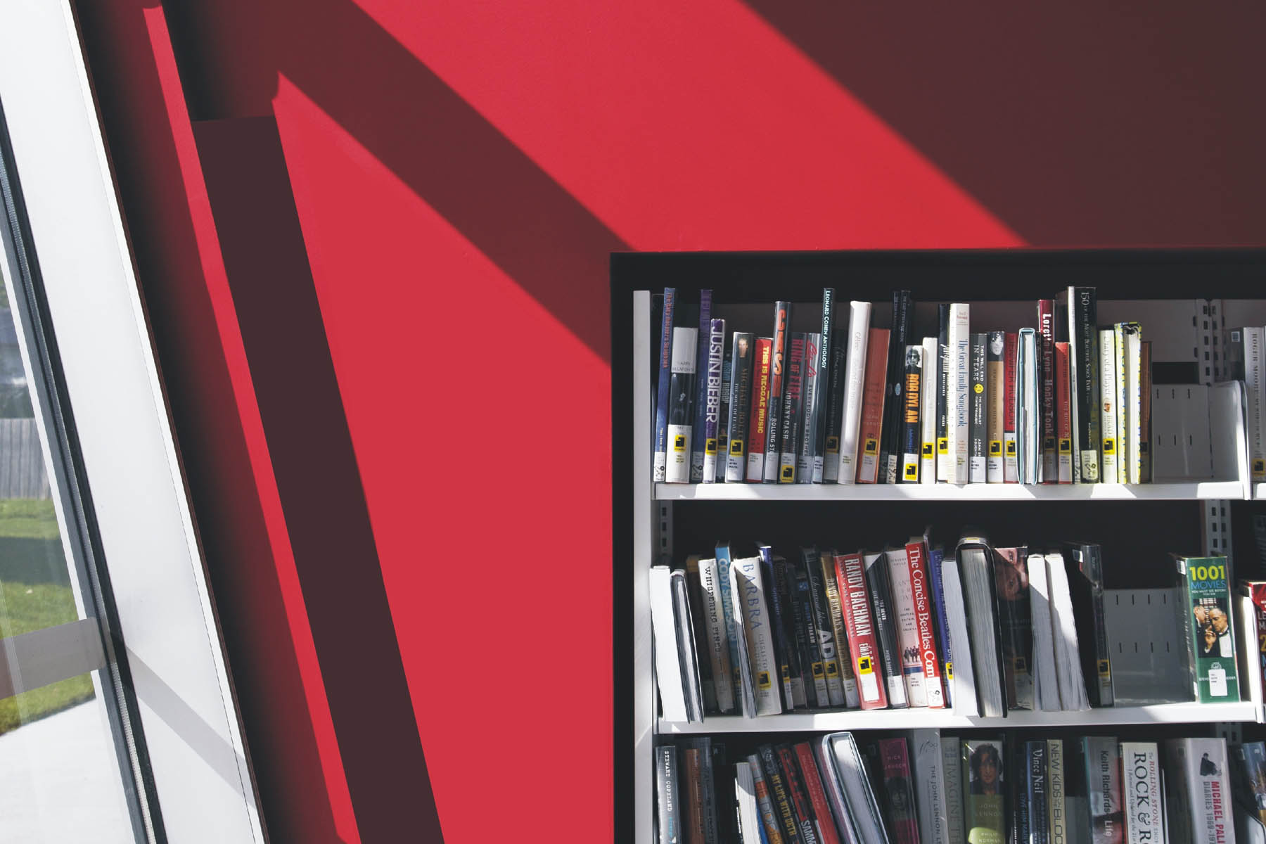 Bookshelf next to slanted glazed wall with sun casting shadows on red painted wall