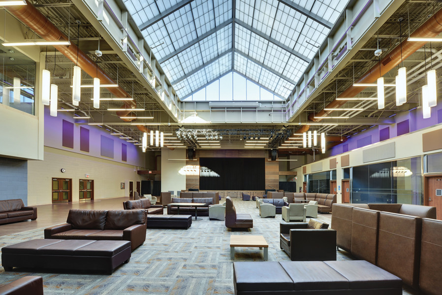 Double height atrium student lounge space with brown leather couches and large skylight and view of stage