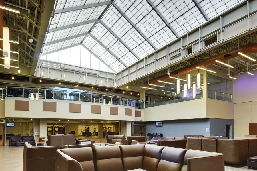 Double height atrium student lounge space with brown leather couches and large skylight