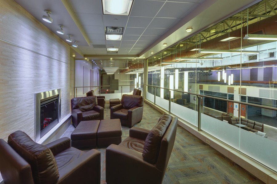 Second storey student lounge space with brown leather chairs surrounding fireplace and glass wall looking down to student lounge space