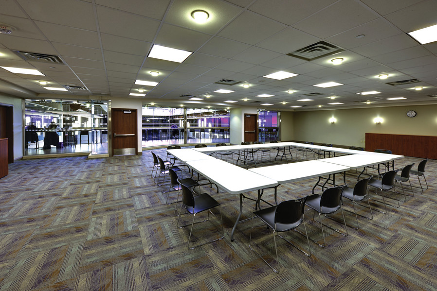 Student collaboration space with large white tables arranged in a square and glass wall looking out to corridor