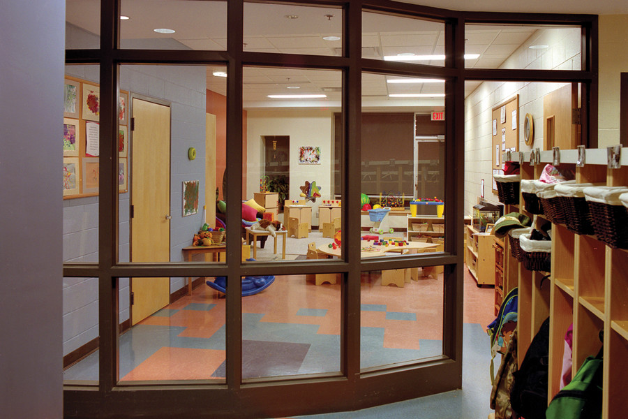 View of glazed day care room filled with children's furniture and toys from cloak room