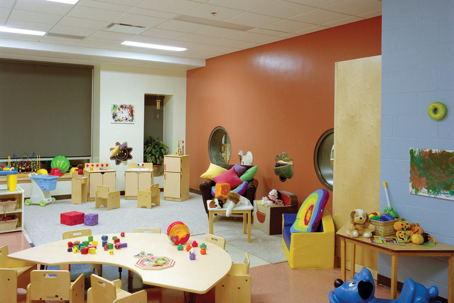 Day care room with orange feature wall with low circular windows looking into adjacent room with children's furniture and toys