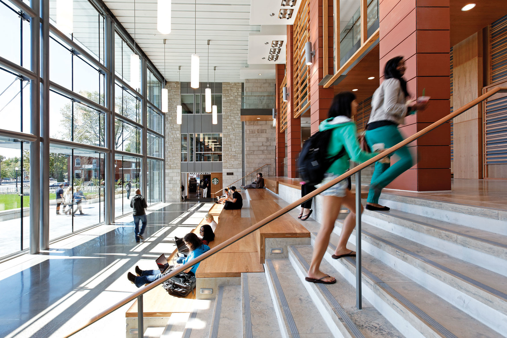Students walking up steps adjacent to large wooden step lounge area with glass facade on left and Starbucks entrance in background