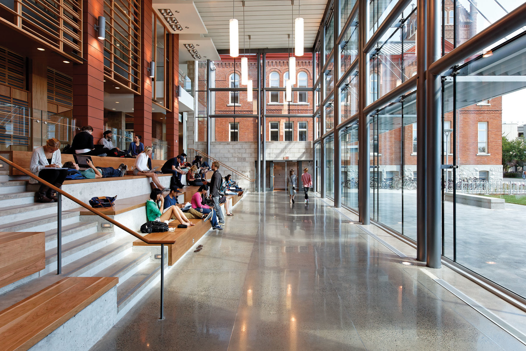 Students lounging on large wooden steps of Learning Commons looking through glass façade to original red brick Victoria School House
