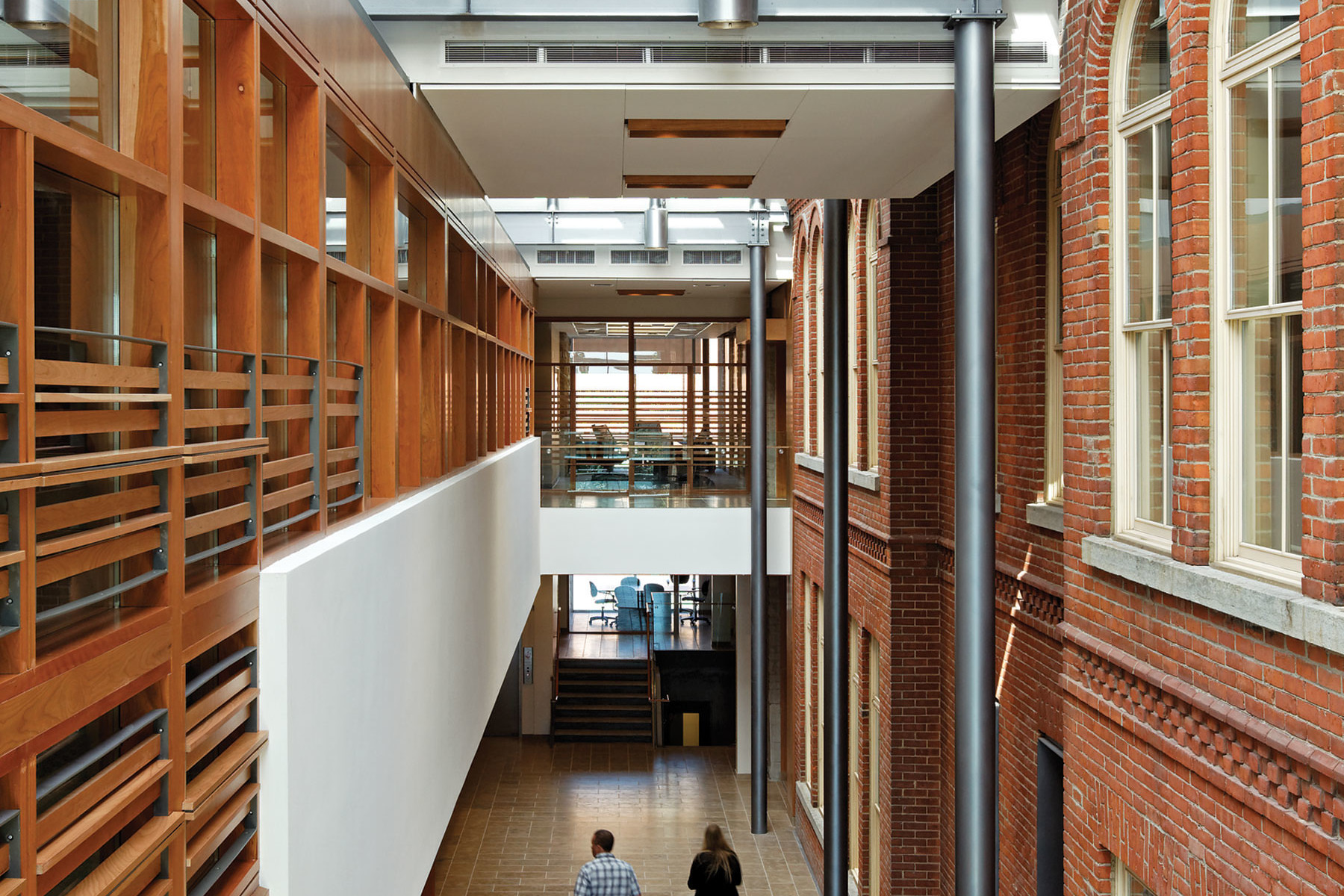 Students walking through double height atrium space with skylights and original red brick facade on right and wood slatted wall on left