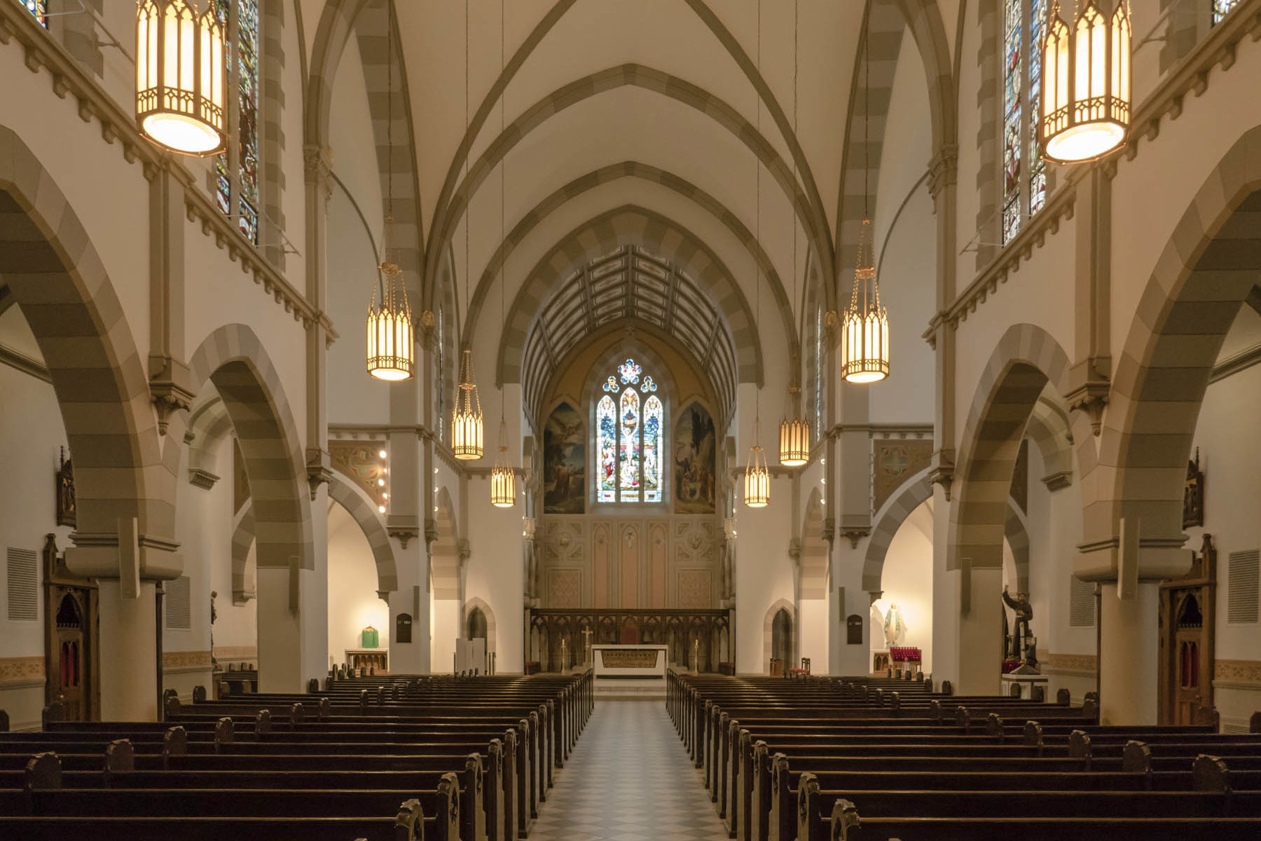 Nave with wood pews, stained glass windows and vaulted ceiling