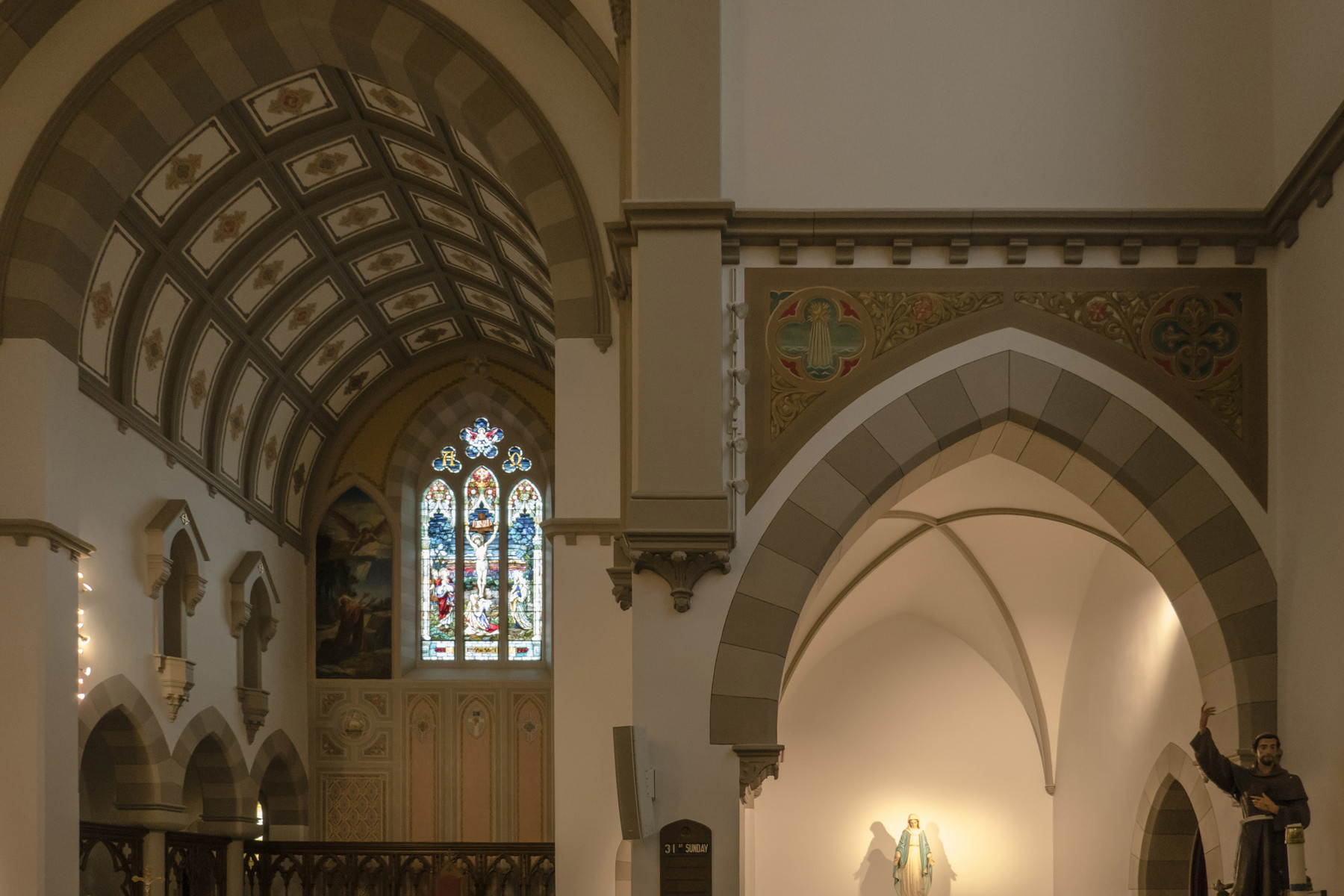 View of Nave from Alter highlighting statue of the Virgin Mary, with wood pews, stained glass windows and vaulted ceiling