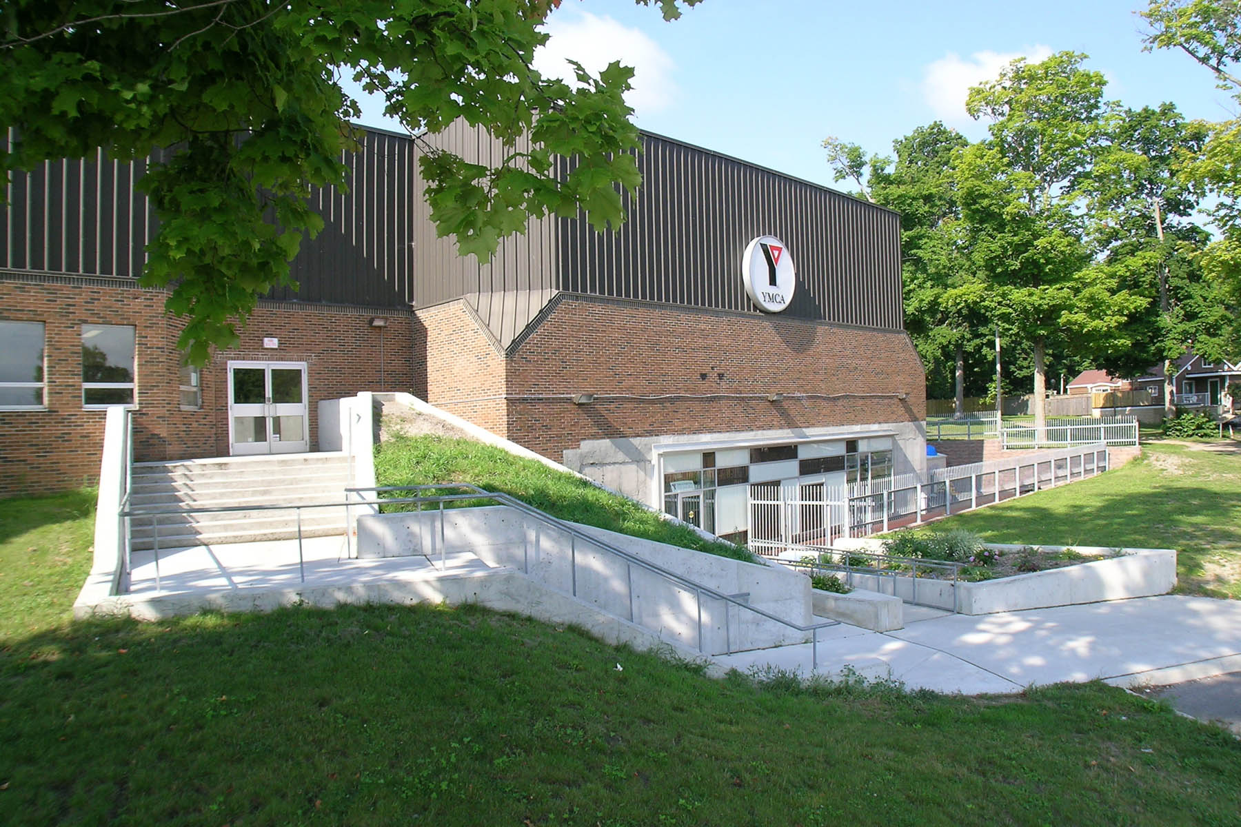 Exterior with the Y logo and staircase entrance to second level and ramp entrance at ground level