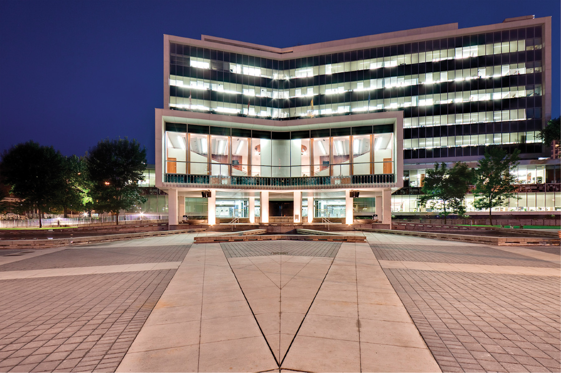 View of illuminated front entrance and building from open courtyard at night