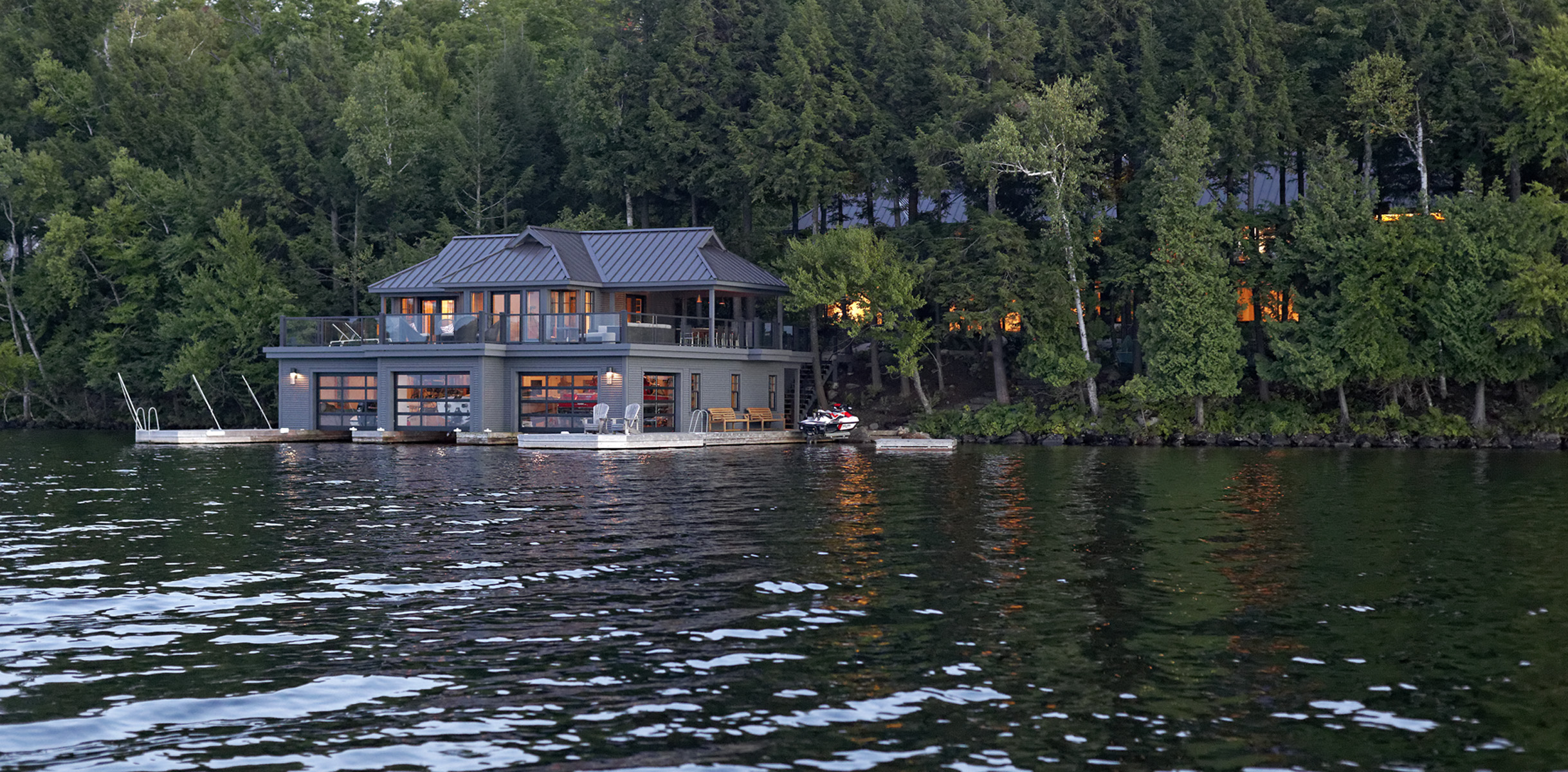 View from lake of illuminated three slip boathouse with living space above with cottage obscured by trees in background