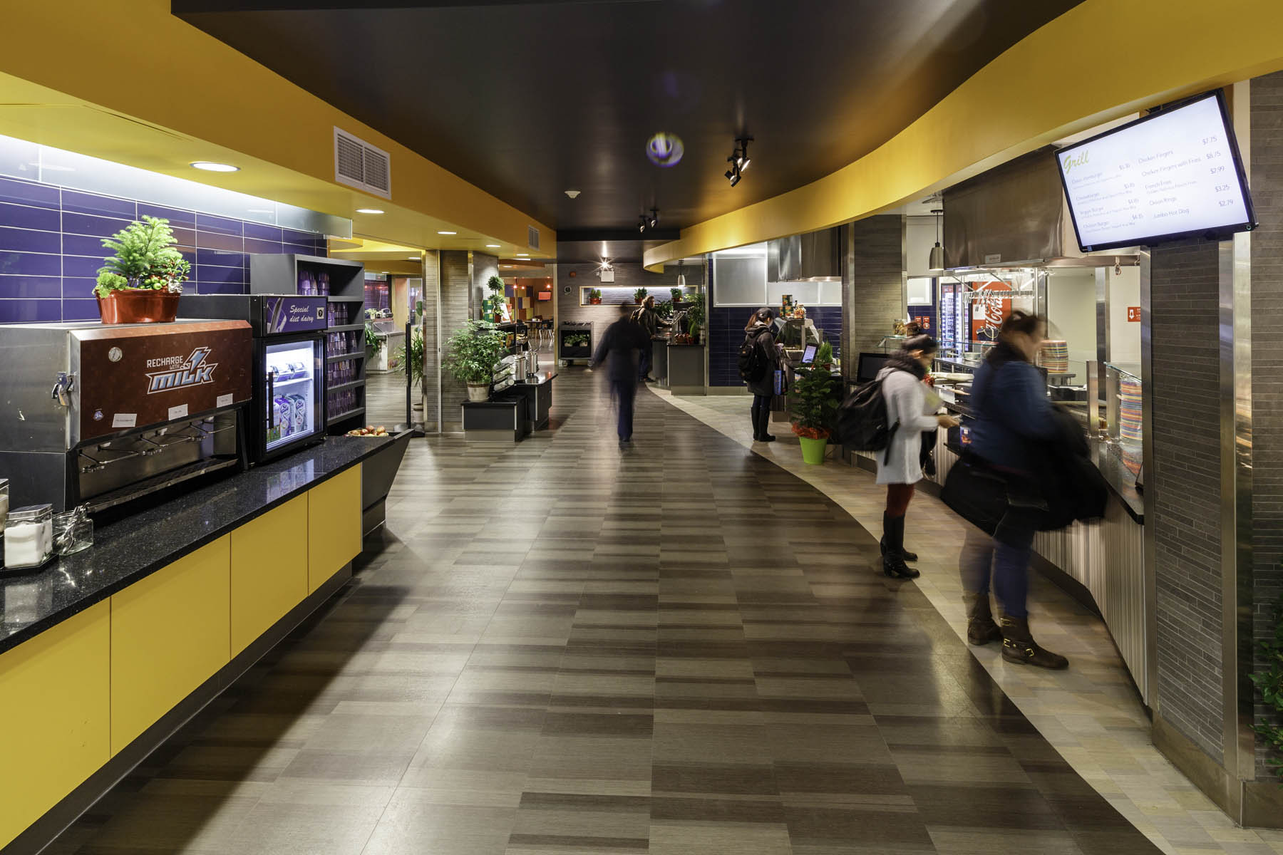 Students browsing food market stalls on right and vending machines on left with yellow counter and ceiling feature