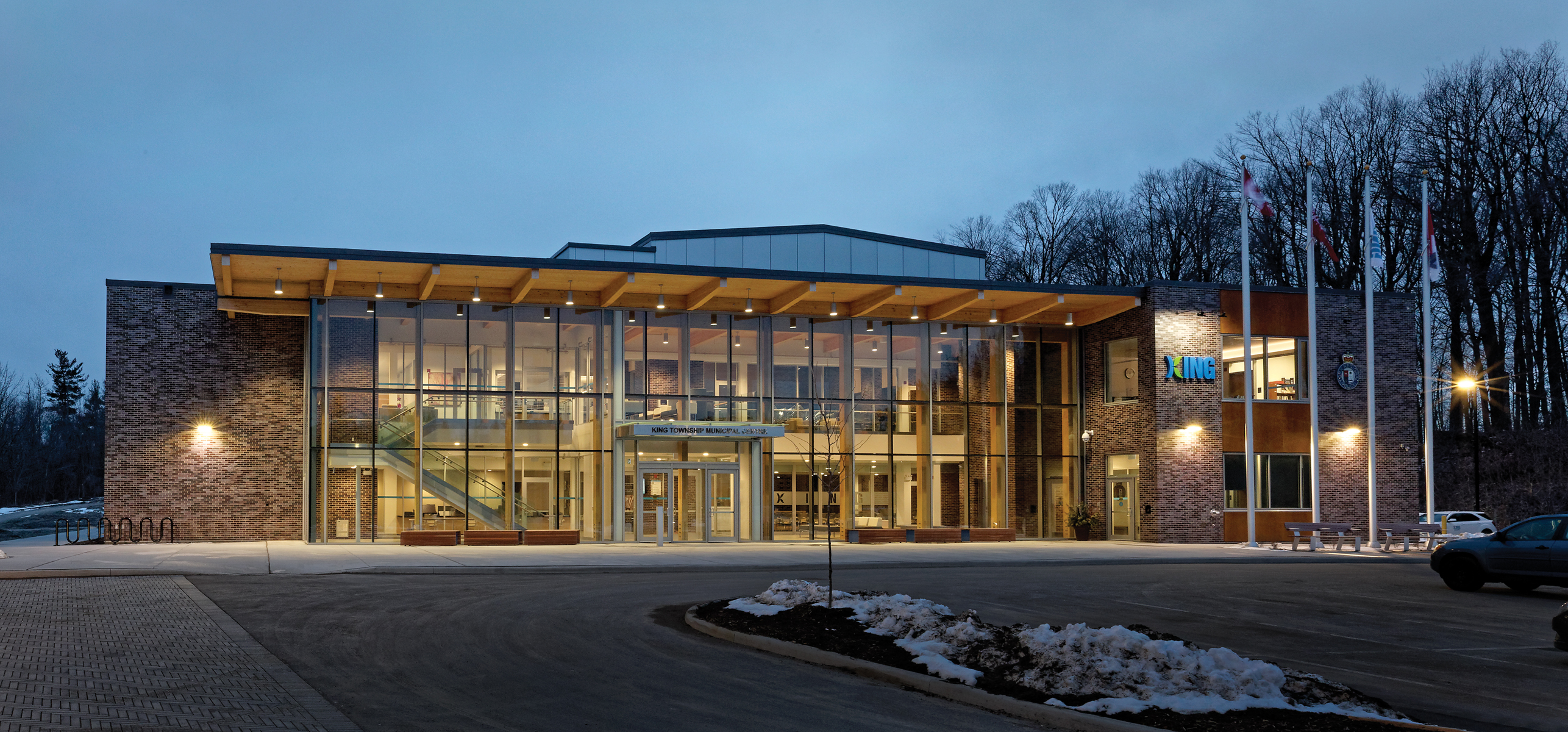 View from parking lot of front elevation of two storey building with illuminated glazed facade