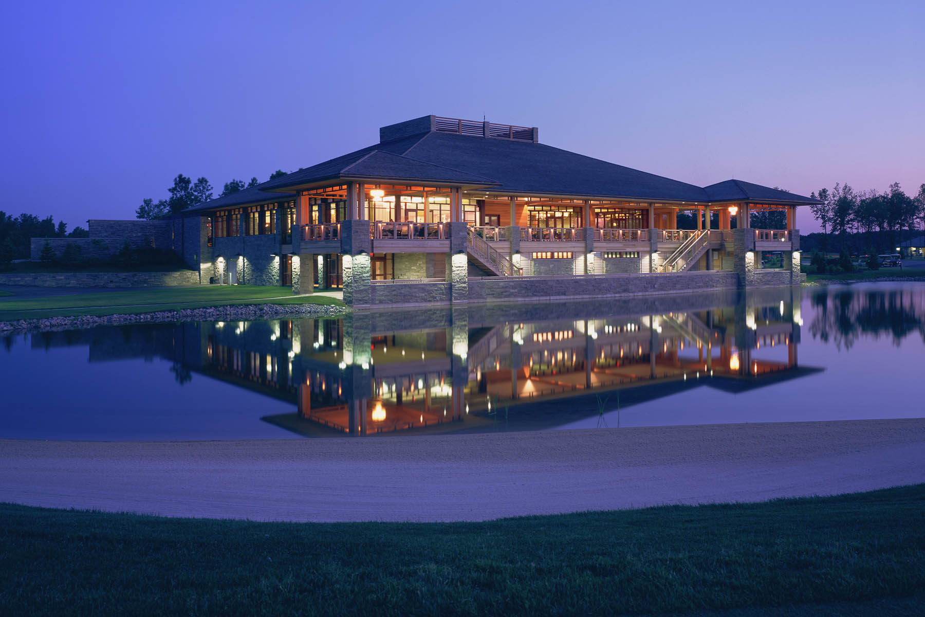 View from illuminated clubhouse on pond with building reflection in water at dusk