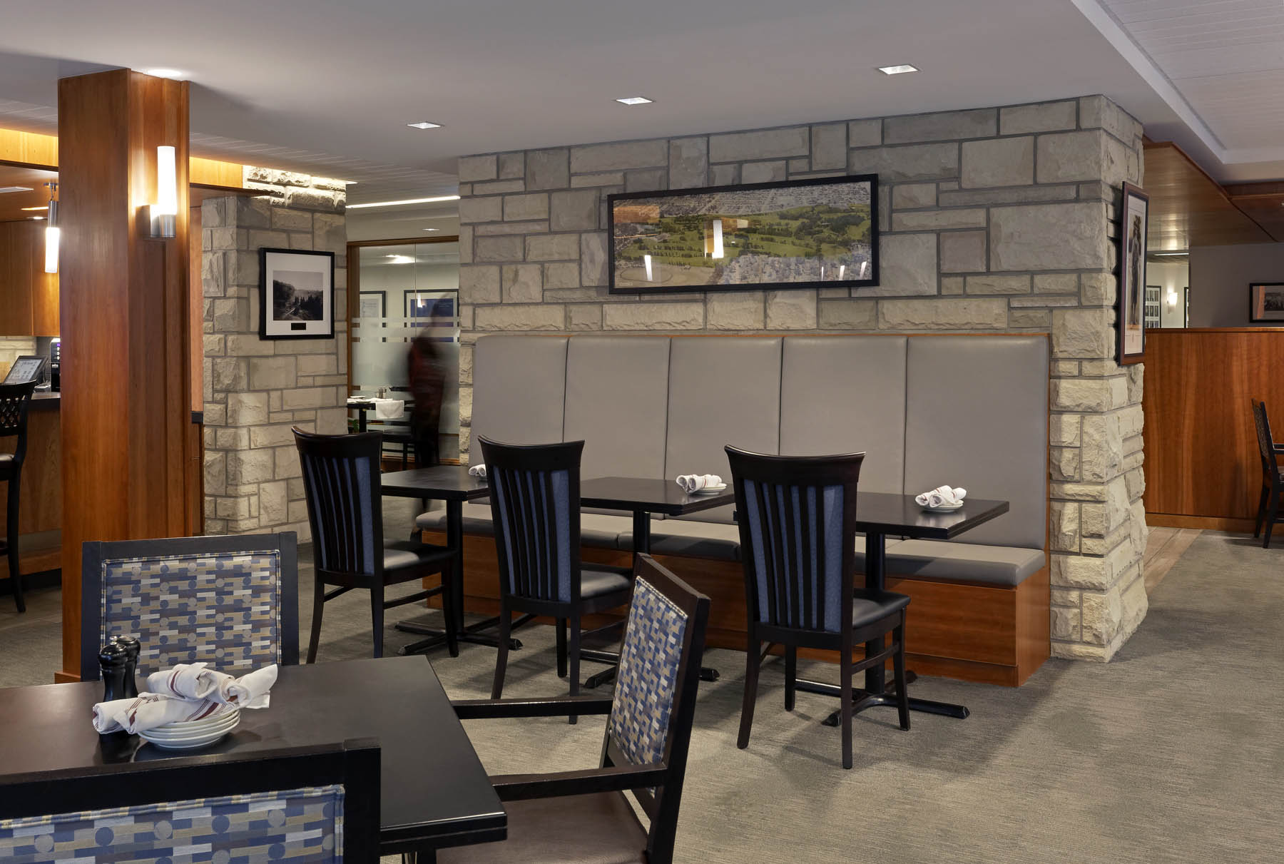 Dining room with grey leather banquet with stone feature wall, and wood columns
