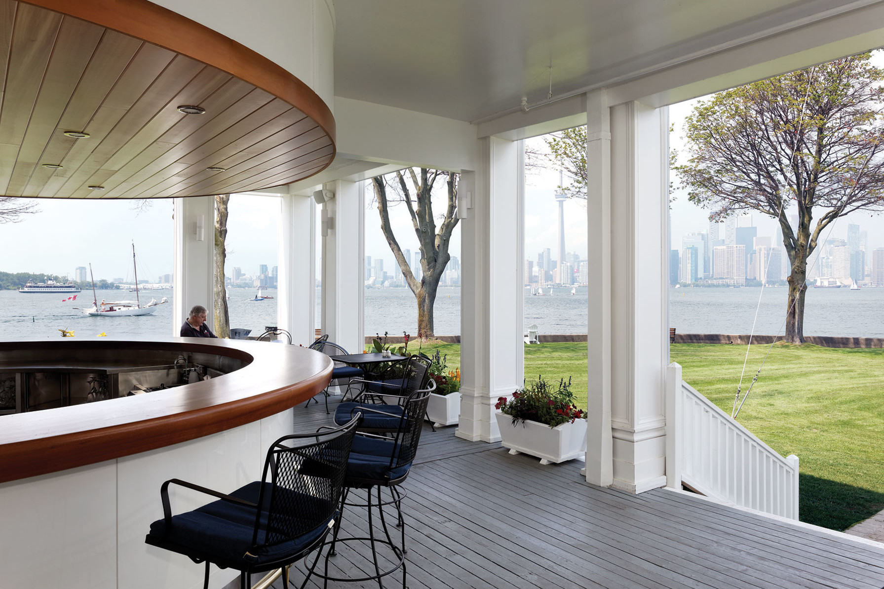 Covered patio with round white and wood trimmed bar overlooking green lawn with trees, lake with sailboats and city scape