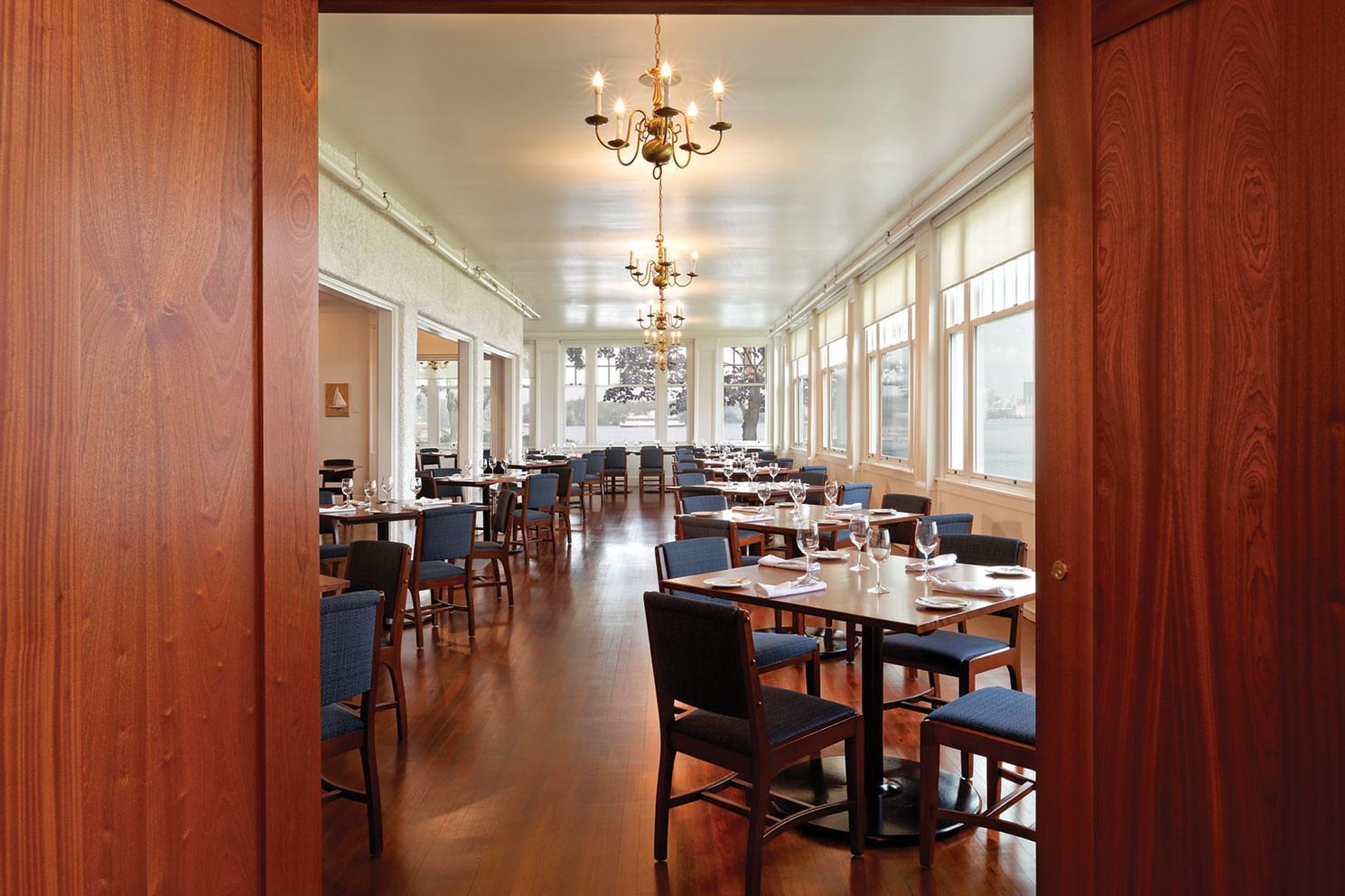 View through open wood doors of white dining room with blue chairs, wood tables and floor, chandeliers, and large windows