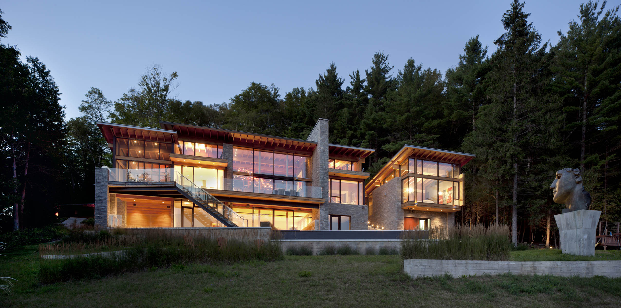 Glass facade of illuminated three storey house with stone feature wall and landscaping at dusk