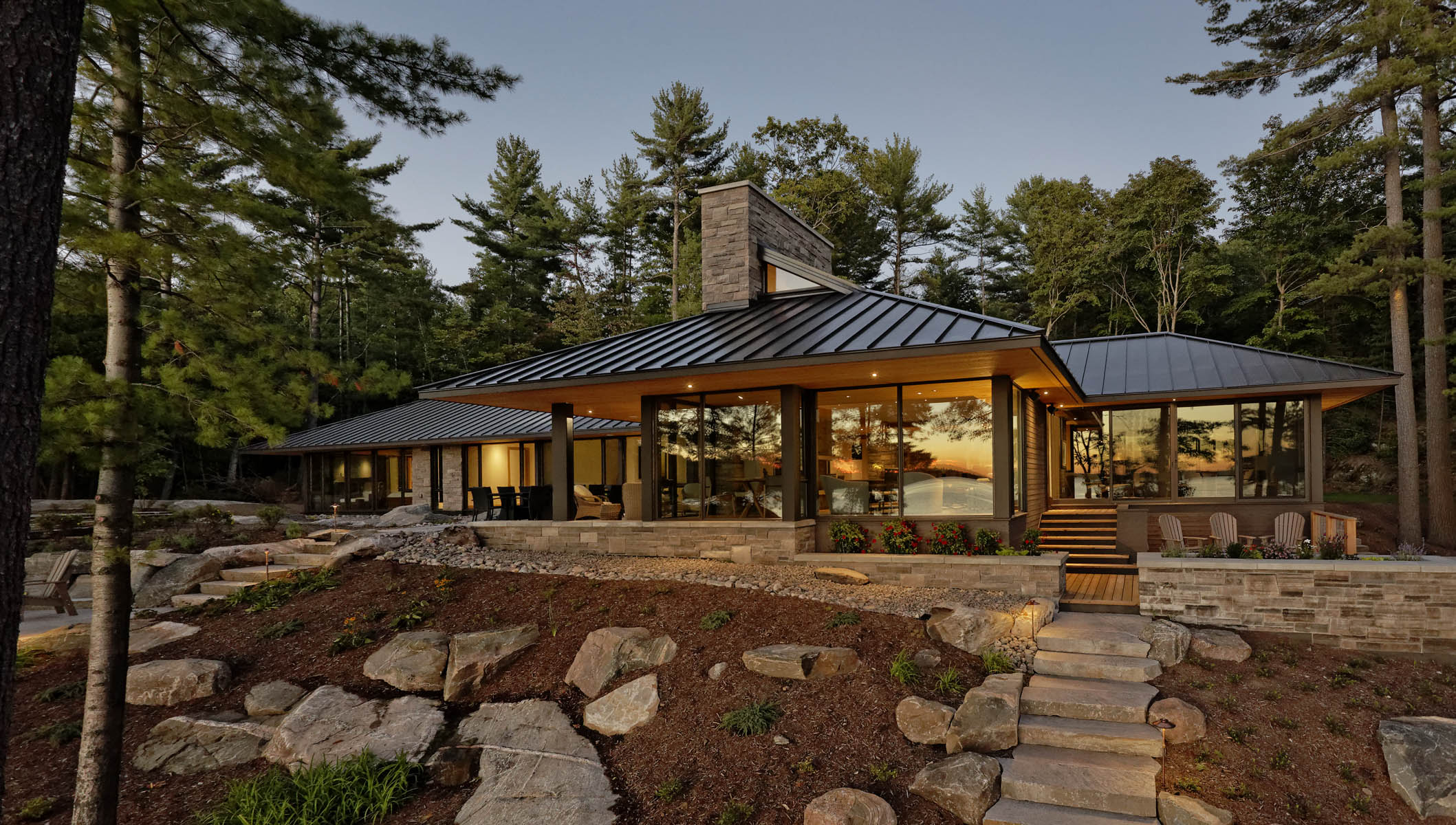 Illuminated cottage elevation with sunrise reflected in windows with rock landscaping in foreground and trees in background